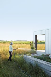 A Sustainably Built Home in Rural Ontario - Photo 3 of 16 - Maggie Treanor waters plants around her rural home.