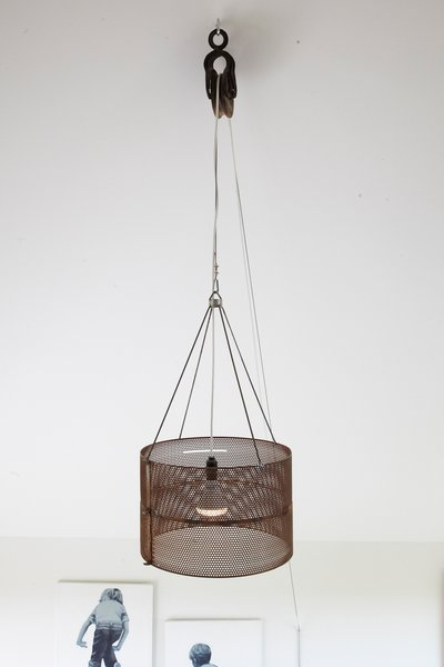 A metal lighting fixture with an adjustable cord hangs from the ceiling.