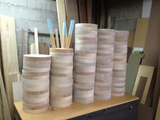 A stack of circular tops lay in wait for their futures as colorful milking stools.