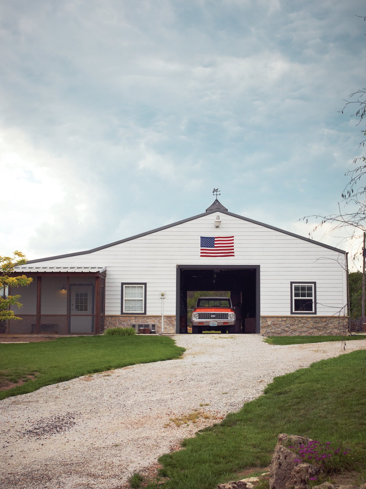 Behind the main house is the barn, where Paul builds furniture and works on cars Tagged: Garage.  Photo 5 of 10 in A Modern Farmhouse Recalls Old-Time Americana