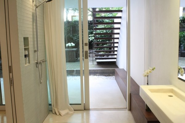 The only separation between the master bath and the backyard is this sliding glass door.