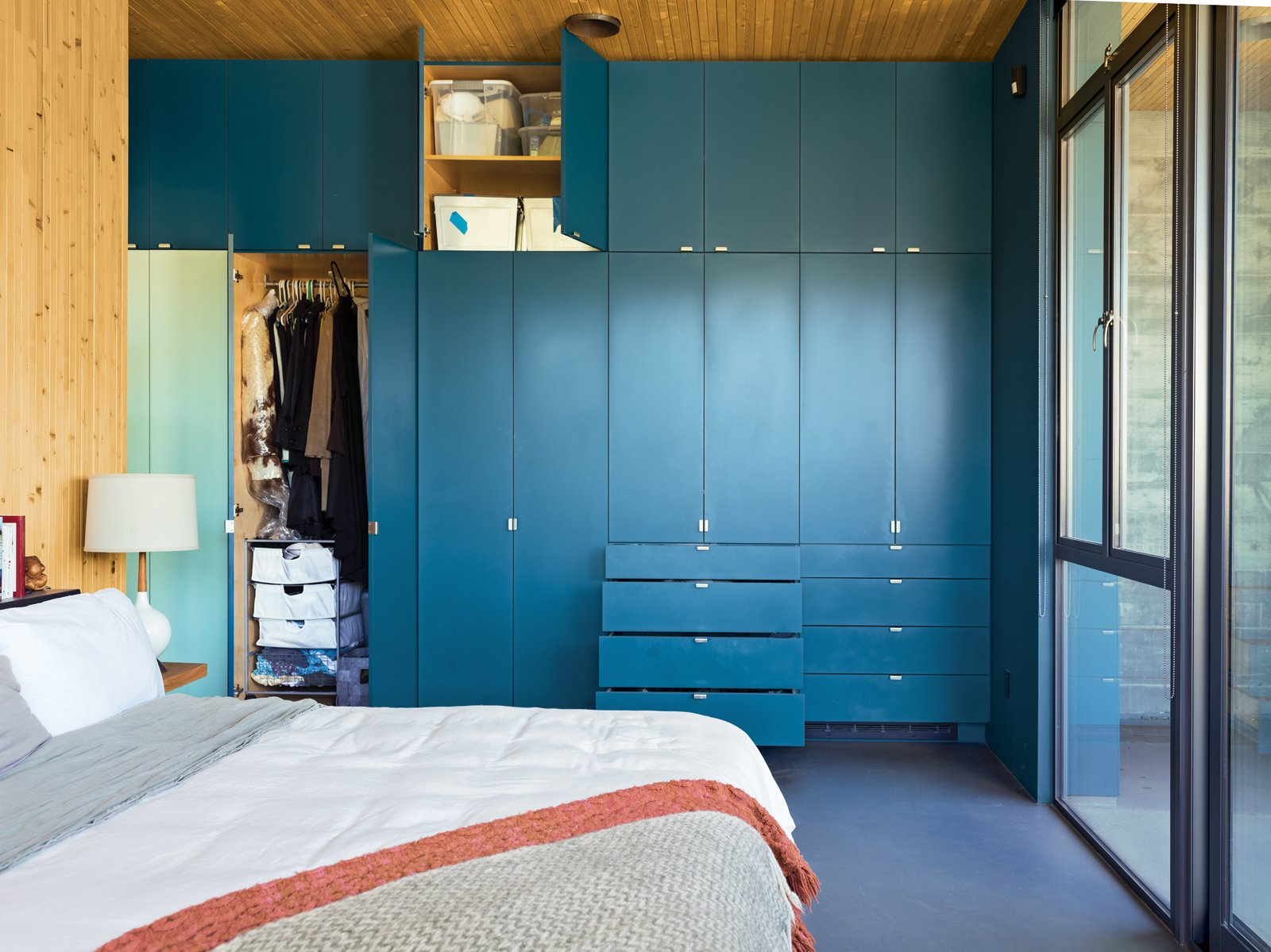 "In such a small space ""you have to organize, and every piece takes a decision,"" says resident Heidi Wright. The couple keep things they use less frequently, like guest bedding, in the higher cabinets. Tagged: Bedroom and Storage.  Photo 5 of 9 in Malibu Canyon House with a View"