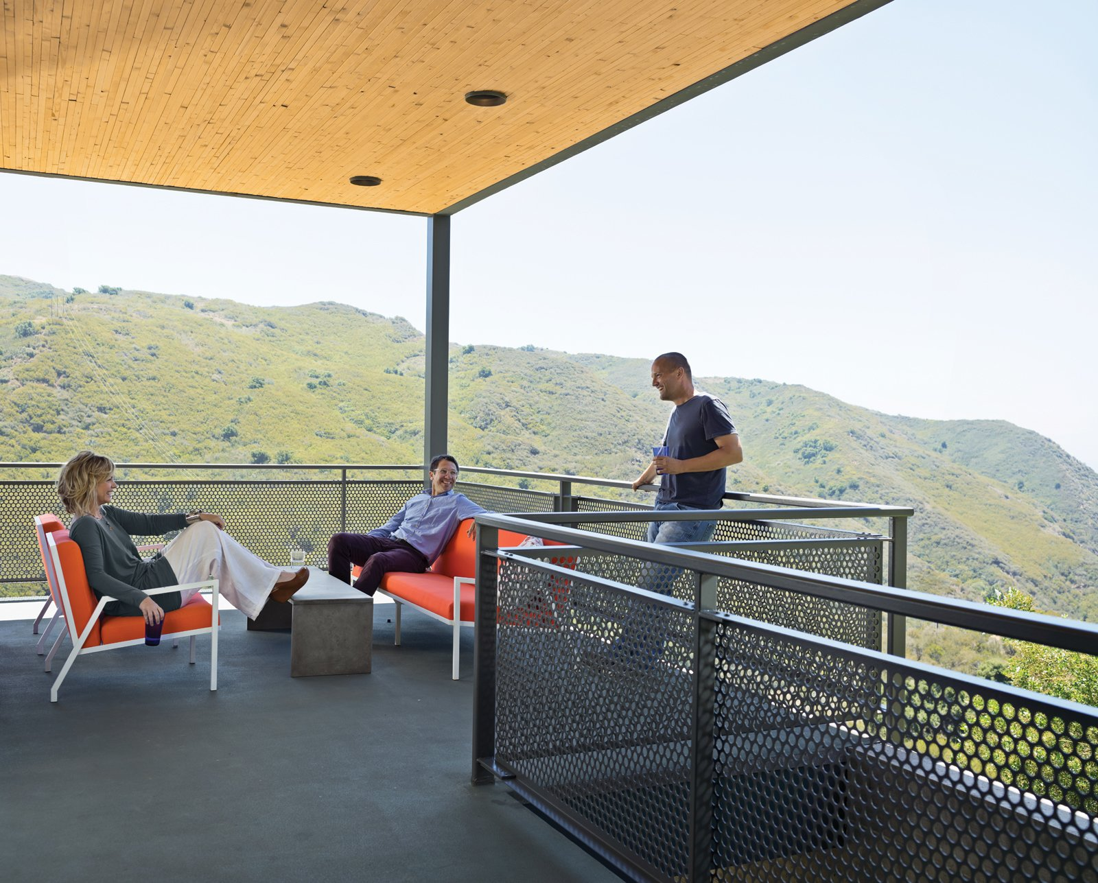 Wright and Keffer (standing) hang out on their deck with Bolander, who lives just across the road. The chairs, designed by Bolander, are upholstered in Sunbrella fabric. Tagged: Outdoor, Large Patio, Porch, Deck, and Concrete Patio, Porch, Deck.  Photo 3 of 9 in Malibu Canyon House with a View
