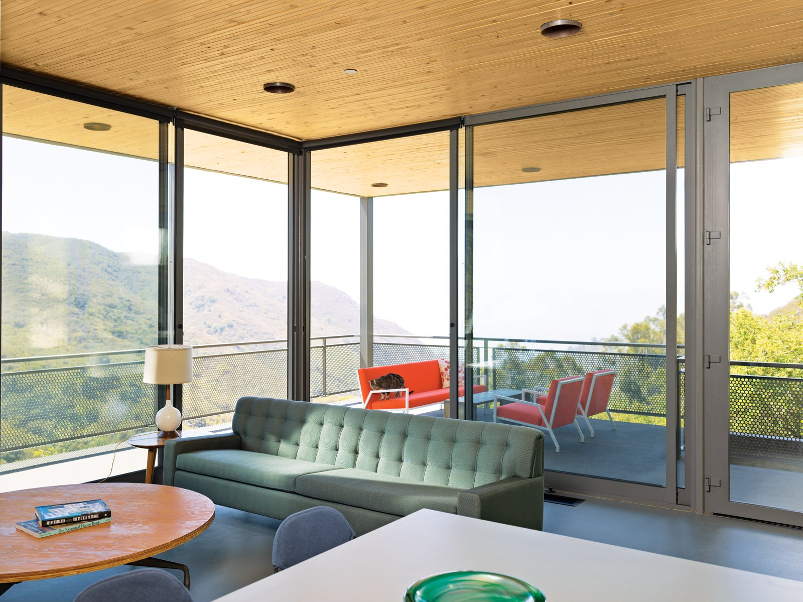 The sofa and lights in the open-plan living, dining, and kitchen area are vintage. Tagged: Living Room, Sofa, Coffee Tables, Table Lighting, and Ceiling Lighting.  Photo 6 of 9 in Malibu Canyon House with a View