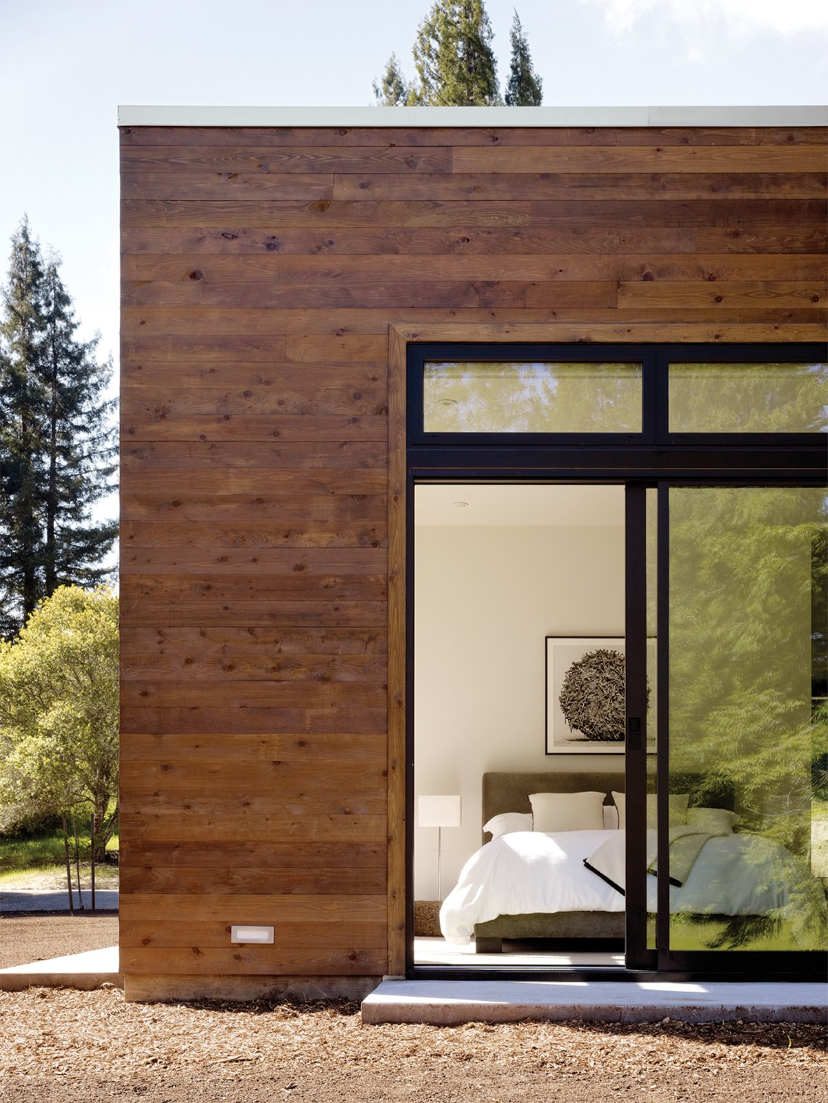 The modestly scaled master bedroom opens to a view of the woods located behind the property. Tagged: Bedroom and Bed.  Photo 4 of 5 in This Couple Achieves Their Glass House Goals