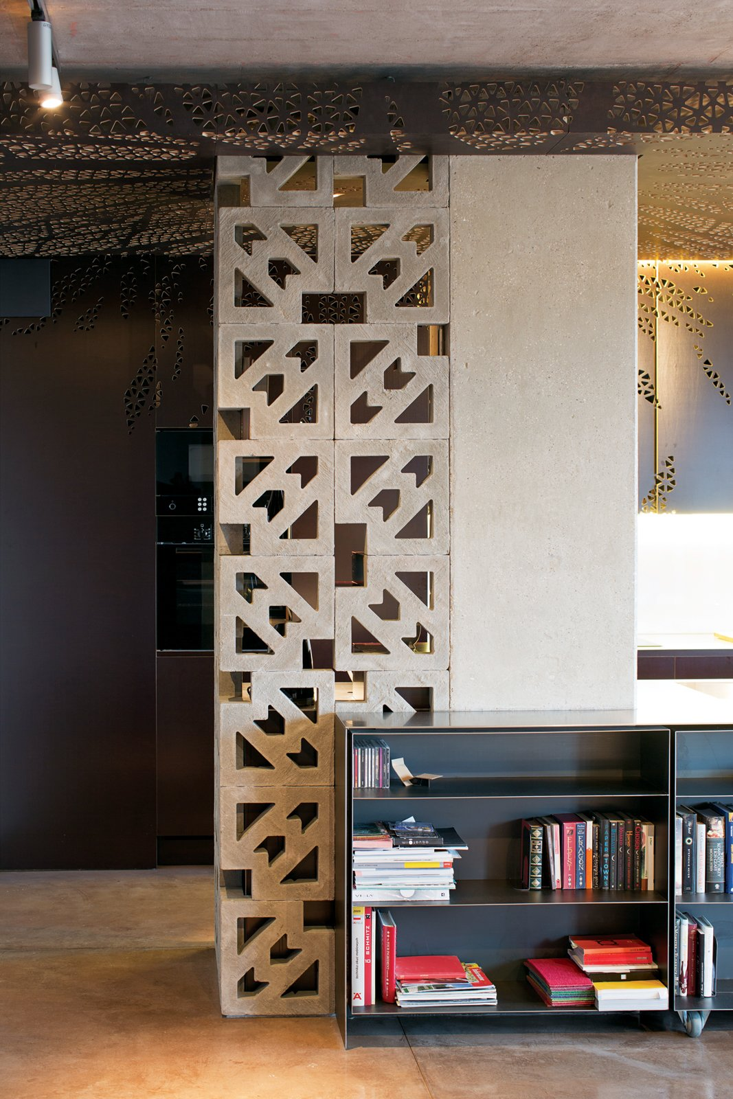"""Ornate concrete blocks screen a storage area in the kitchen while letting light through. The effect is """"romantic—romantyczny,"""" says Nix.  Photo 5 of 9 in Warsaw Loft with Multifunctional Furniture"""