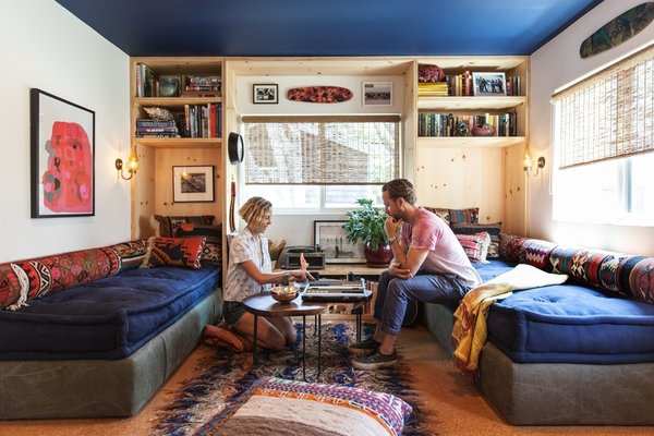 Howard and Shumate in the living room, where Commune designer Steven Johanknecht introduced custom built-in daybeds with storage beneath. The carpet-fragment pillows are from Commune, as is the table, designed by Joshua Tree–based sculptor Alma Allen. The poster is by Mike Mills.