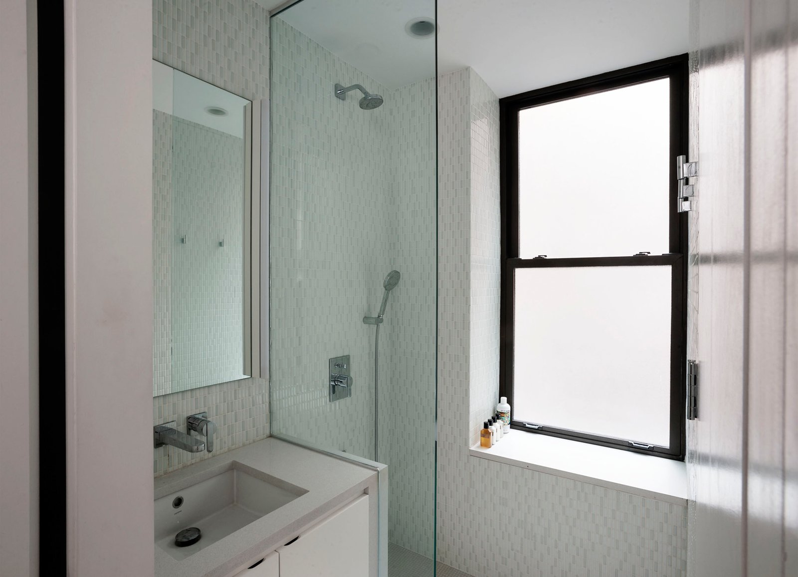 In the shower a pre-existing window sill was used to create a comfortable shower seat, while the glass enclosure keeps the bathroom feeling open.
