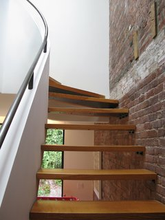 Thick planks lead visitors up the staircase and compliment the wooden-beam details left exposed from the previous layout.