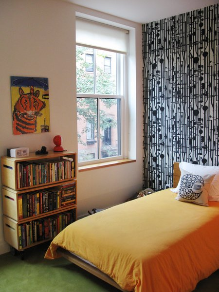 The children's bedroom features bright carpeting and patterned wallpaper.