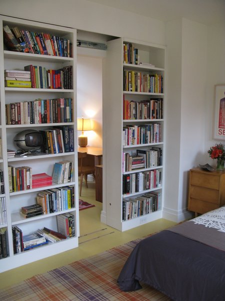 Bookshelf walls in a guest bedroom slide to reveal a small study.