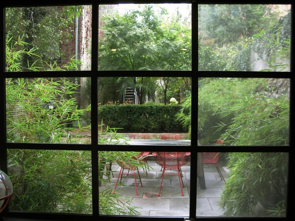 Here's a view of the garden through custom steel windows fabricated for the house by the owners' artist friend.