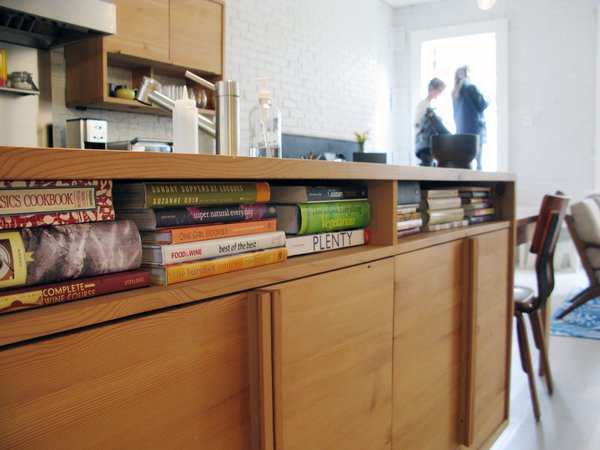 "Cubby holes under the kitchen counter house cookbooks. The cabinets are made from salvaged wood. ""The kitchen is where they like to be at home,"" Bischoff says. ""That's why it's in the middle of the floor plan."""