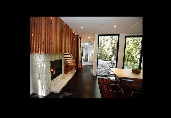 The interior metal grating motif is continued in these stairs made out of redwood from a tree on-site. A centrally located gas fireplace distributes heat evenly throughout the home as an energy-saving measure.