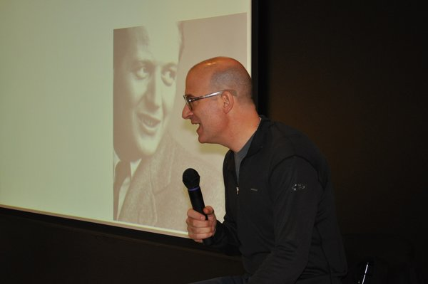 Pardo talks onstage with Knoll founder, Hans G. Knoll, projected on the screen behind him.