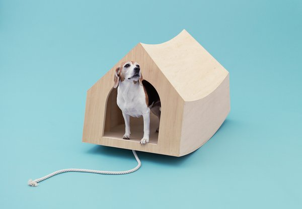 """Dutch architects MVRDV were assigned the beagle, a """"curious and playful"""" breed the firm thought should have some power <br><br>of its own. An optional cord attached to the portable birch plywood structure means Fido can use the entire thing as a pull toy. <br><br>At rest, the pooch palace riffs on the traditional Snoopy-esque doghouse silhouette with its simple interior and gabled roof; <br><br>at play, it becomes a see-saw reminiscent of MVRDV's own Balancing Barn."""