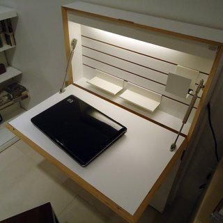 One of the pieces installed in the model apartment is a fold-out desk cabinet called the Flatmate that's only four inches deep when closed. It features built-in interior lighting, cubbyholes along the sides for storage, and a power strip.