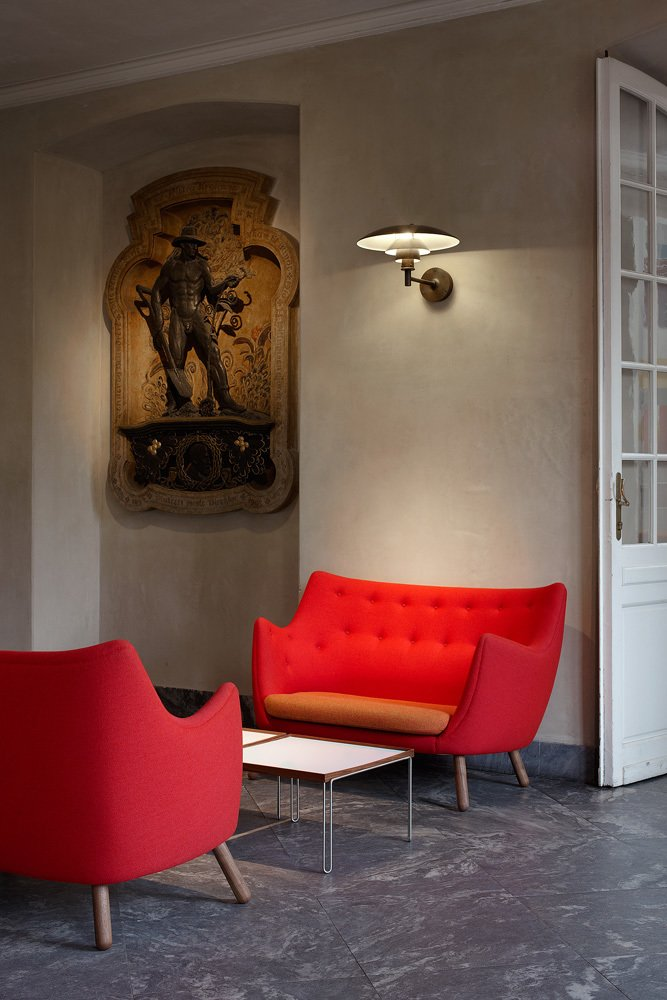 """Two bright red Poet sofas face off in the vestibule leading into """"Furniture for the Senses."""" Juhl designed the sofas in 1941 for use in his own home (more on that to come!).  Finn Juhl Centennial at Designmuseum Danmark by Kelsey Keith"""