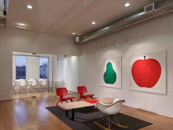 "Red, green, and white reduce the visual clutter of the office. The conference room gets plenty of natural light and the wall, coated with Idea Paint (TM) is used for brainstorming project ideas. ""We get a lot of natural light. Light is really important to me, personally. I don't perform well when I'm in a dark, enclosed space. We wanted to keep it really clean because we deal with color all day long,"" says Pum. Photo by: Anice Hoachlander of Hoachlander Davis Photography"