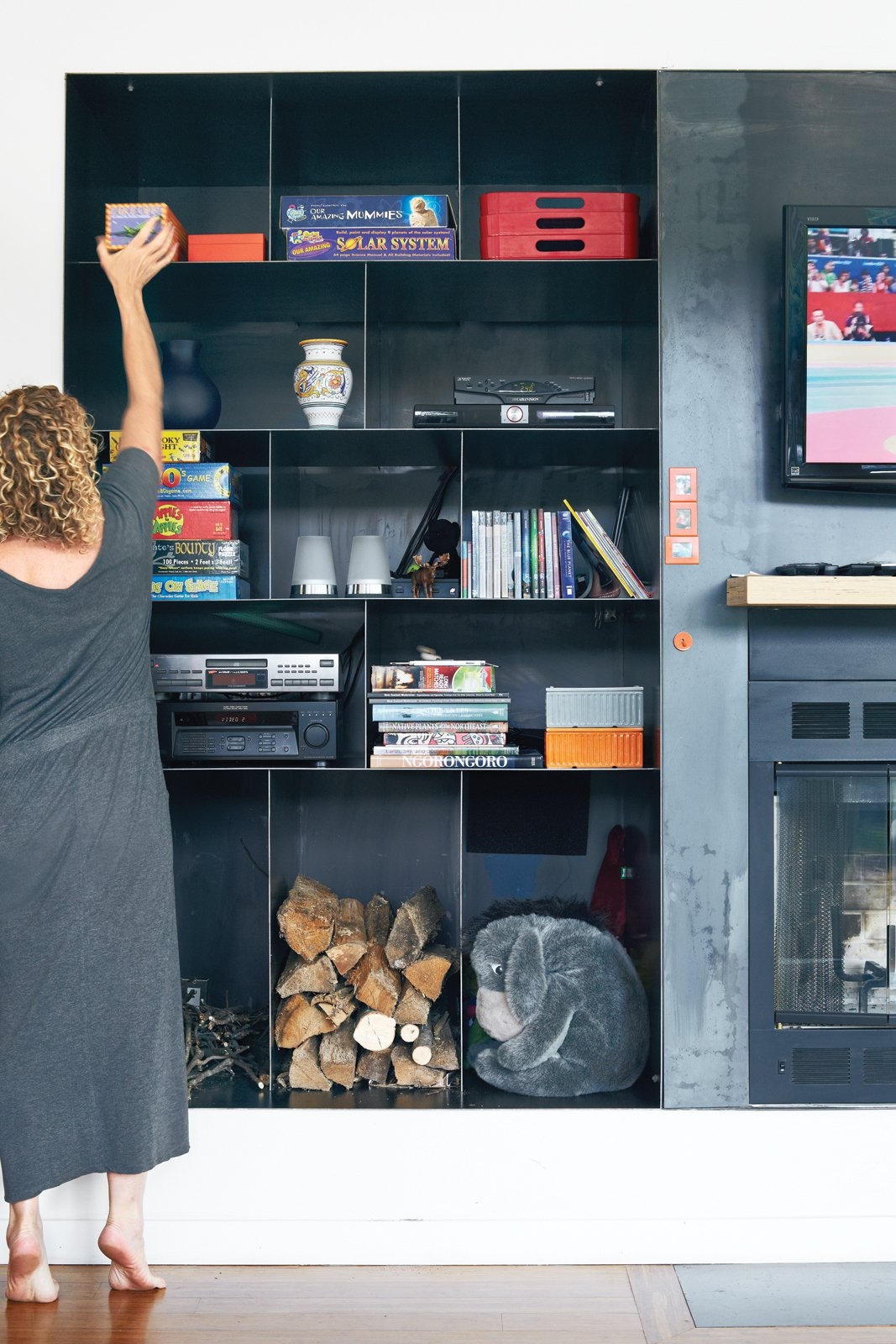 """Three-For-One: Gibbs says the custom hot-rolled black steel storage unit in the living space's one exterior wall was the architects' """"baby."""" Having only one unit to house a television, a fireplace, and wood storage was a top priority. Even in the """"baking hot"""" summer months, she says, """"My son wants to roast marshmallows.""""  monessenhearth.com"""