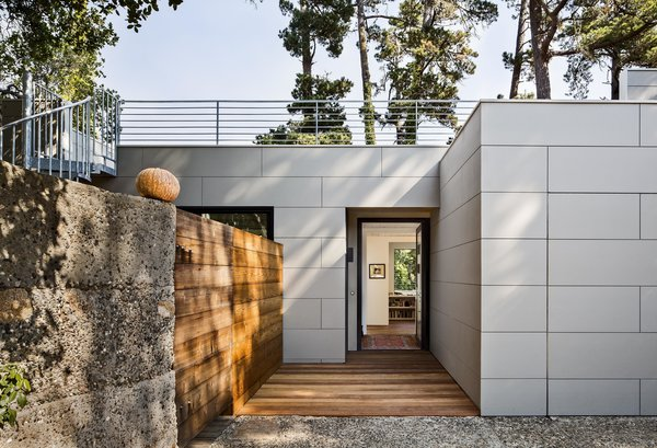"""Architect Mary Ann Schicketanz transformed the old entryway into a private courtyard, replacing the door and window with a sleek glass slider. She removed the fiberglass panels and constructed a reclaimed wood barrier to separate the sitting area from the new front door on the opposite side. A high concrete wall also encloses it. """"I love that you can be right on the street without having any sense the street is there,"""" Schicketanz says. Photo  of Torres House modern home"""