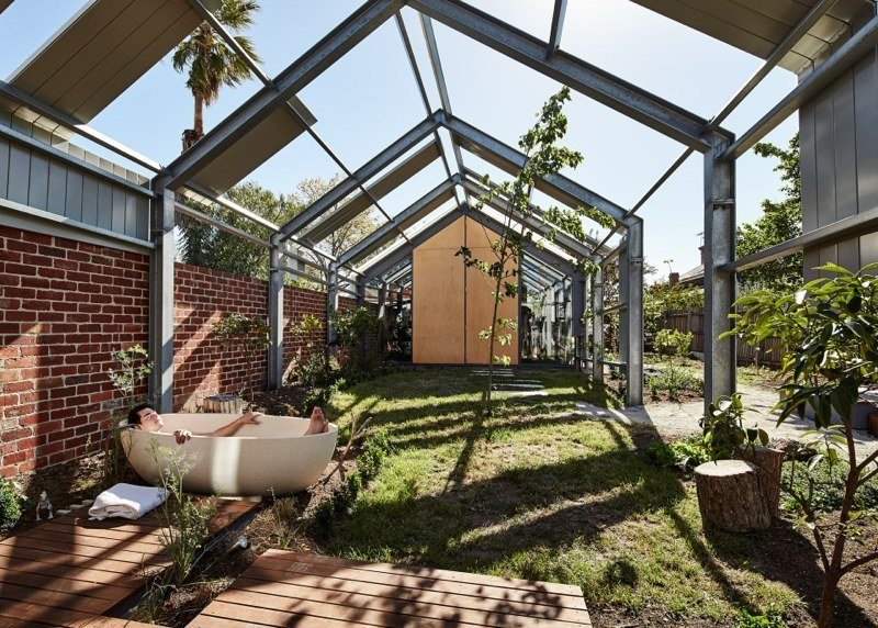 """The outdoor area features an Apaiser tub. Opposite the house, on the other end of the garden, sits a music studio. """"We are aiming to have the garden and house flow into each other,"""" says resident Michelle.  Cut Cut Paw Paw by Allie Weiss from Striking Backyard Transformations"""