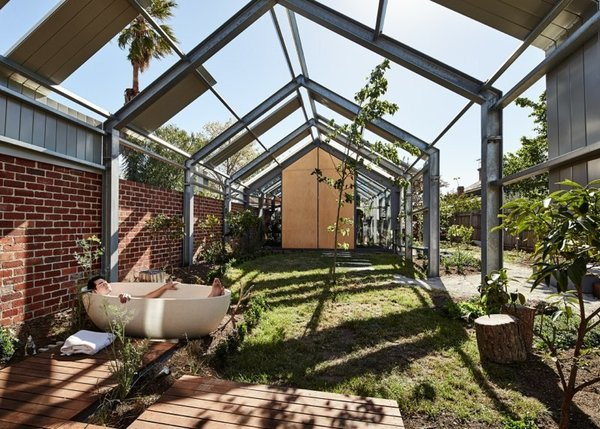 """The outdoor area features an Apaiser tub. Opposite the house, on the other end of the garden, sits a music studio. """"We are aiming to have the garden and house flow into each other,"""" says resident Michelle. Photo 4 of Cut Cut Paw Paw modern home"""