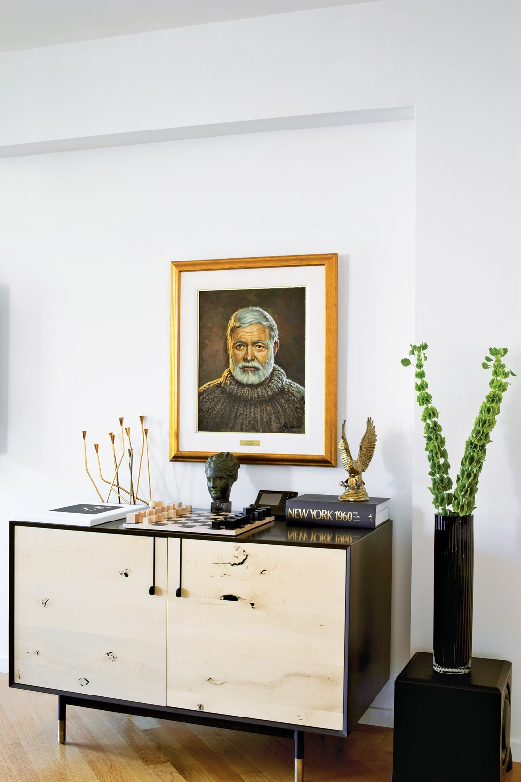 In the living room, a Lake credenza by BDDW is topped with a Bauhaus chess set and a portrait of Ernest Hemingway by the artist Yuriy Rudnev.