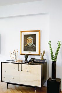 A Renovated Flat in Moshe Safdie's Habitat '67 - Photo 6 of 8 - In the living room, a Lake credenza by BDDW is topped with a Bauhaus chess set and a portrait of Ernest Hemingway by the artist Yuriy Rudnev.