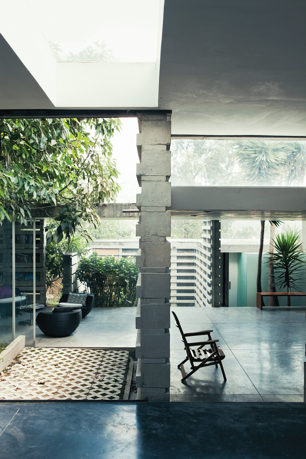 Once past the main threshold, the house opens up to the outside, literally and figuratively. Three courtyards built around existing trees flow seamlessly into a series of rooms with glazed walls and sliding glass doors. Tagged: Living Room and Chair.  Latin America's Best Modern Homes by Kelsey Keith from An Innovative Modular Building System in Ecuador