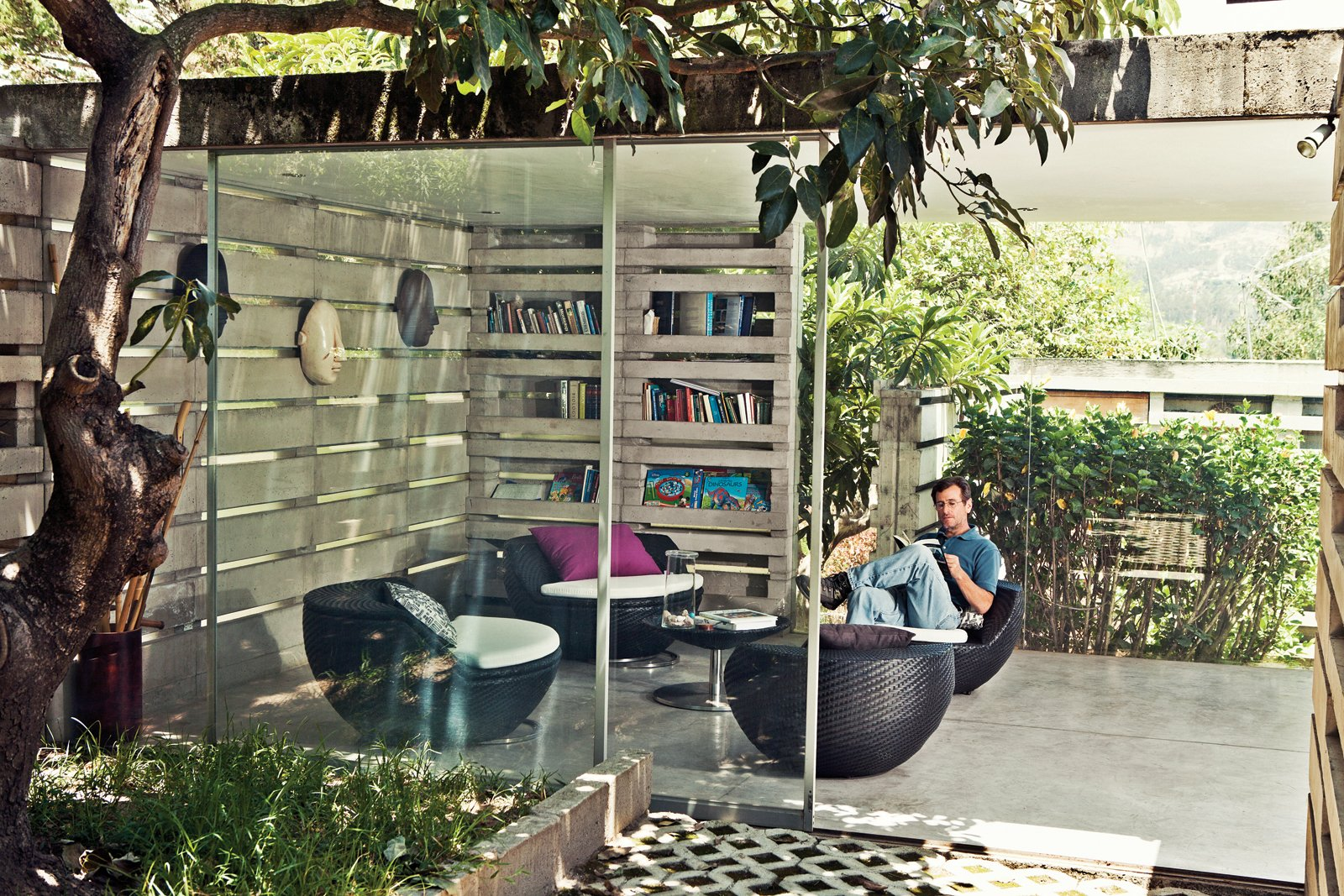 """Herman Pasternak, an engineer and consultant who designs water treatment systems, is a childhood friend of Pentimento's owner, Desirée Marín, and now rents the house. He selected woven plastic chairs from Dream Works, a local company, for his reading room because they """"go with the inside-outside concept of the house."""" Tagged: Living Room, Concrete Floor, and Chair.  Photo 2 of 10 in An Innovative Modular Building System in Ecuador"""