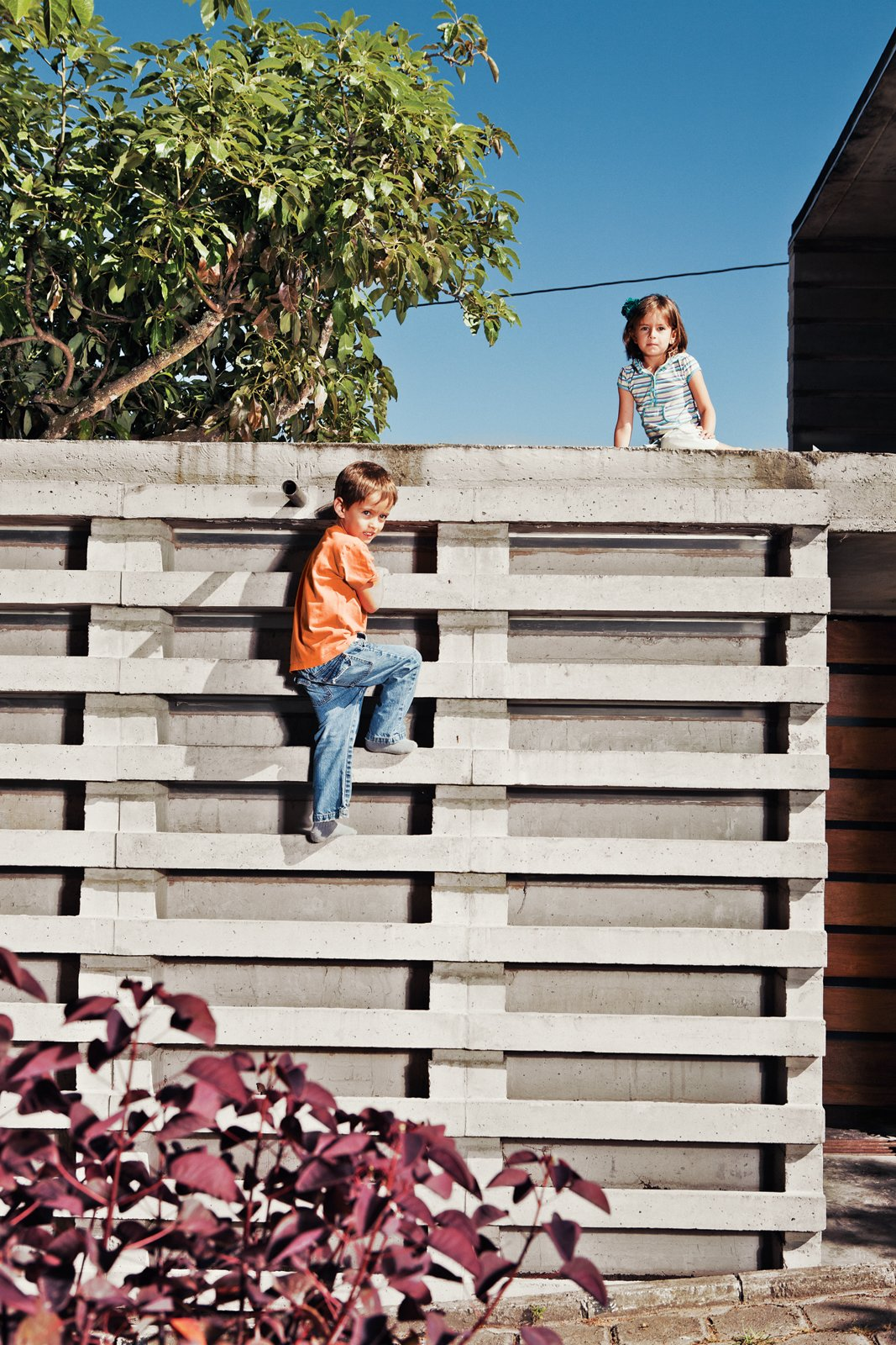 """Six-year-old twins Nicolas and Constanza use Pentimento as their """"little battleground,"""" says Pasternak. """"They have some options here that they will not find anywhere else."""" Among those options are a climbing wall offering easy access to the roof. Tagged: Outdoor and Concrete Fences, Wall.  Photo 6 of 10 in An Innovative Modular Building System in Ecuador"""