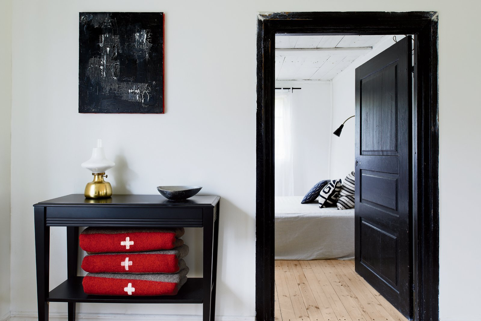 A black side table rests outside the bedroom hallway. Best Photos