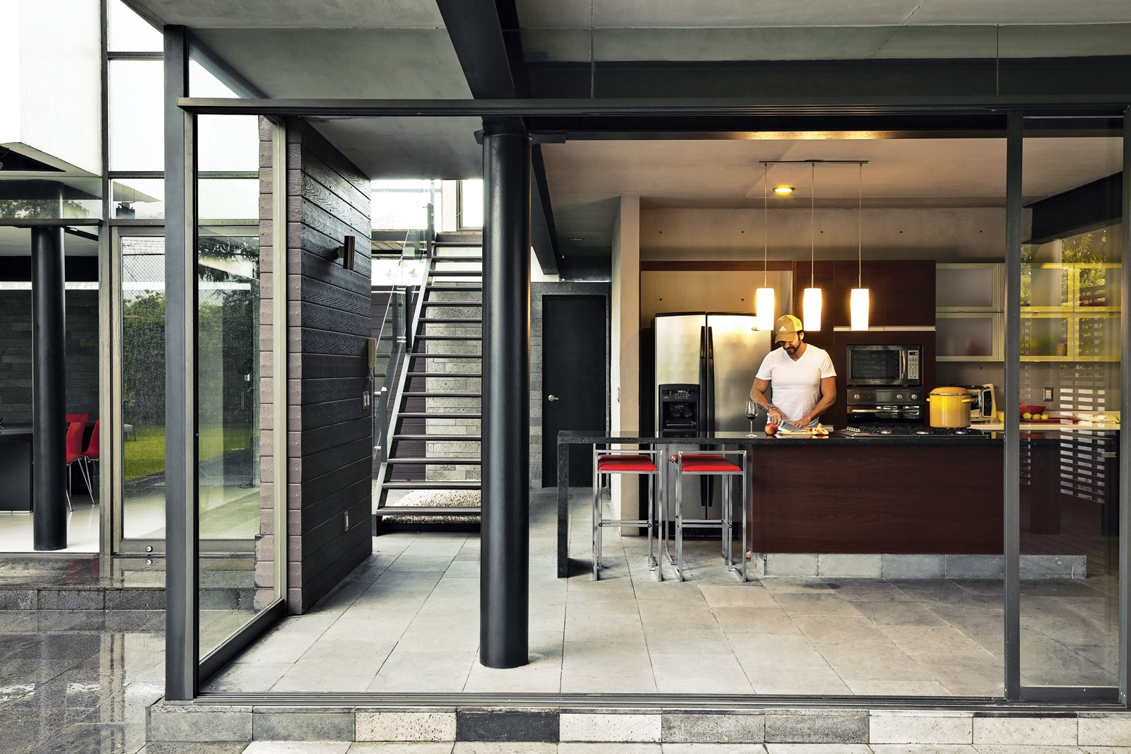 Alfredo chops away in the kitchen, which features floor-to-ceiling sliding glass walls. Tagged: Kitchen, Granite Counter, Refrigerator, Pendant Lighting, and Wall Oven.  Indoor-Outdoor Retreats in Mexico by Allie Weiss from An Affordable High-Design Vacation Home in Mexico