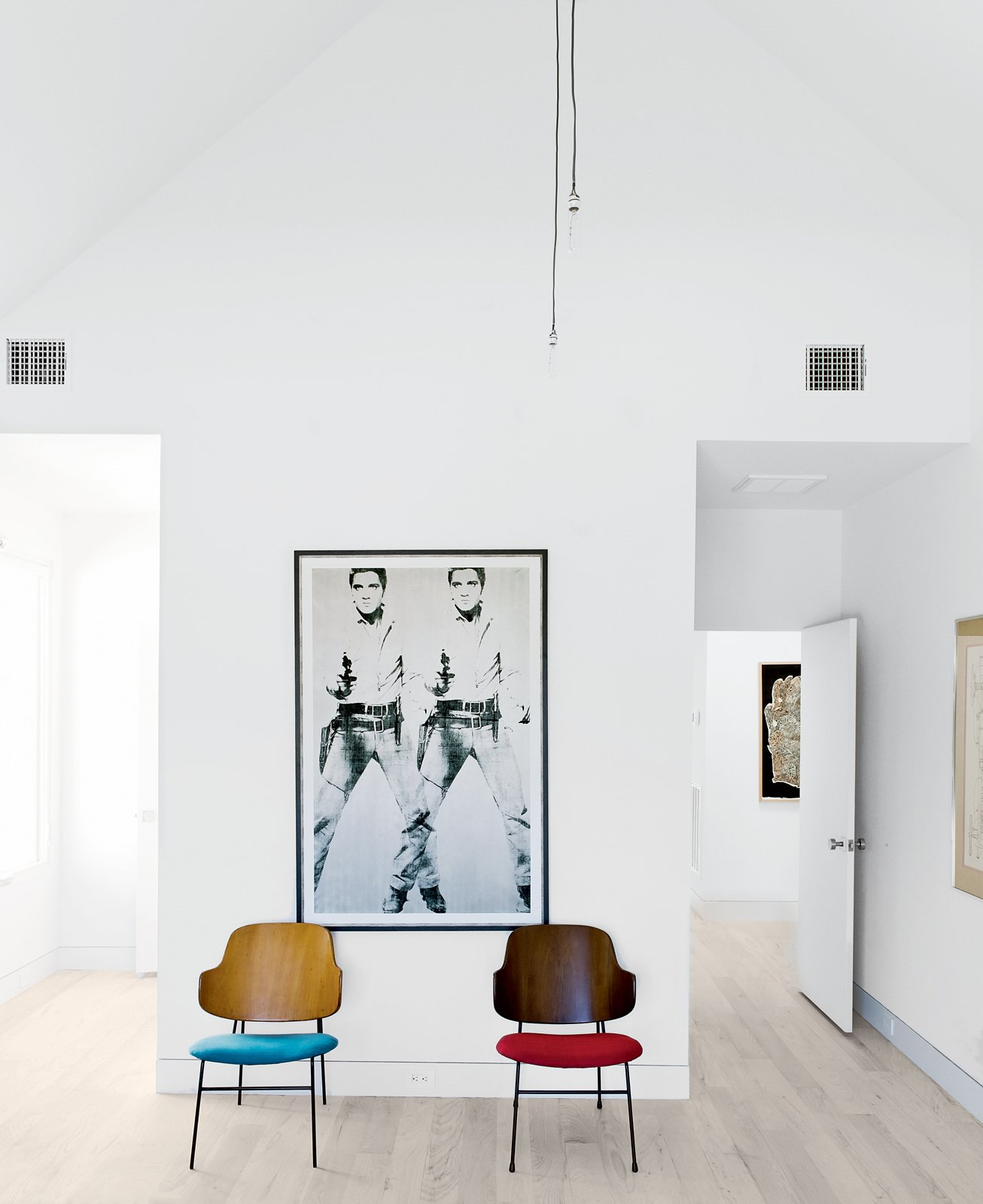 A pair of mid-century perches by Kofod-Larsen sit beneath a print by Andy Warhol in an upstairs bedroom.  Photo 4 of 15 in Row on 25th: Affordable Housing Development in Houston