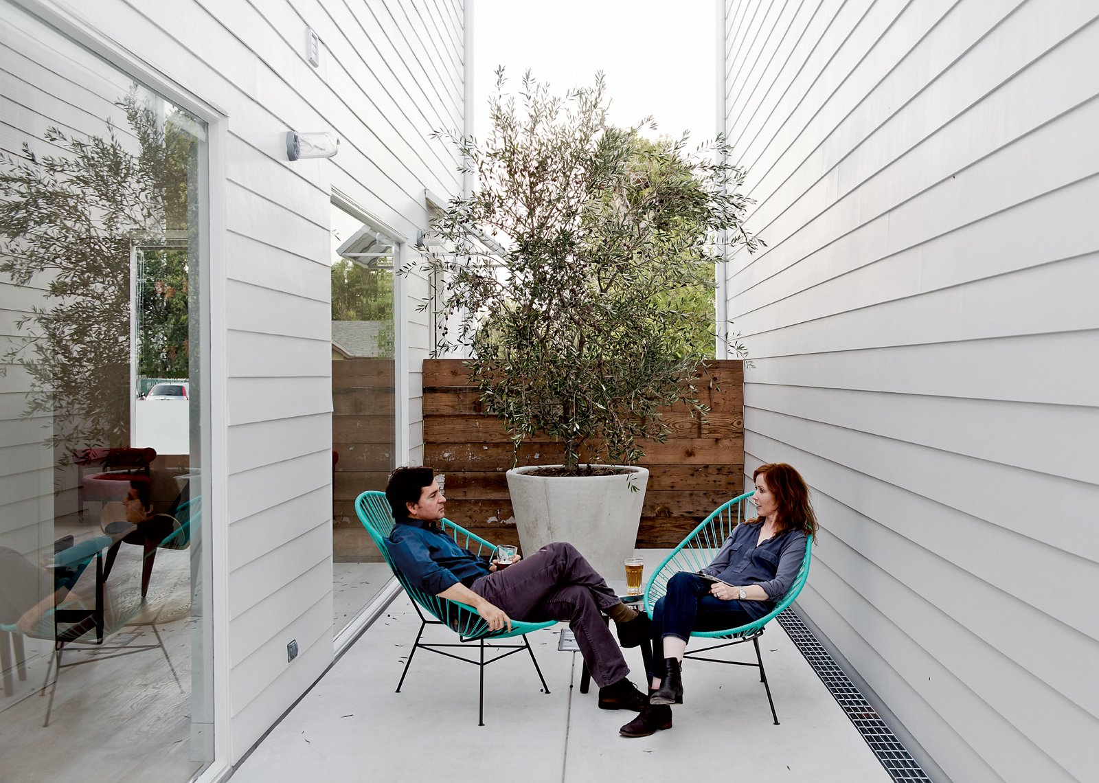 Shannon and his wife, Amy, take the air on a small patio in two Acapulco chairs. Tagged: Outdoor, Small Patio, Porch, Deck, and Concrete Patio, Porch, Deck.  Photo 9 of 15 in Row on 25th: Affordable Housing Development in Houston