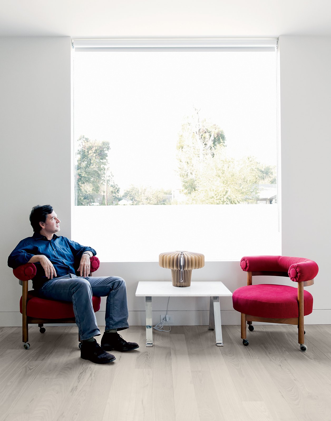 """Designer Barbara Hill recollects that Shannon wanted a """"young, funky feel"""" to his home on the Row. He sits in a vintage chair next to a Satsuma lamp by Jonas Damon for Areaware. Tagged: Living Room, Chair, and End Tables.  Photo 8 of 15 in Row on 25th: Affordable Housing Development in Houston"""