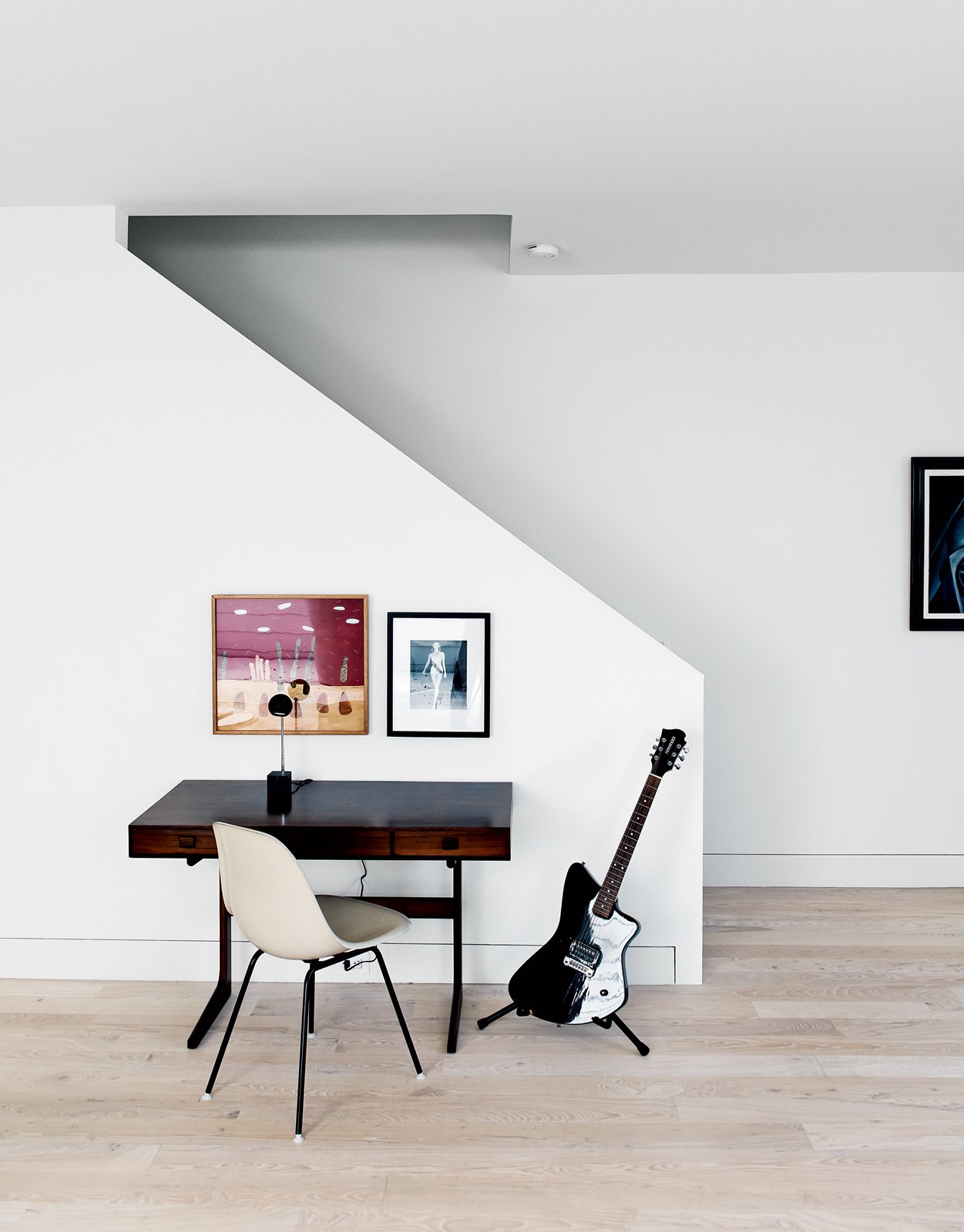 A black electric guitar, a vintage rosewood desk, and a side chair by Charles and Ray Eames sit at the foot of the stairs just beneath a photo of designer Barbara Hill herself competing in the 1956 Miss America Pageant.  Photo 11 of 15 in Row on 25th: Affordable Housing Development in Houston