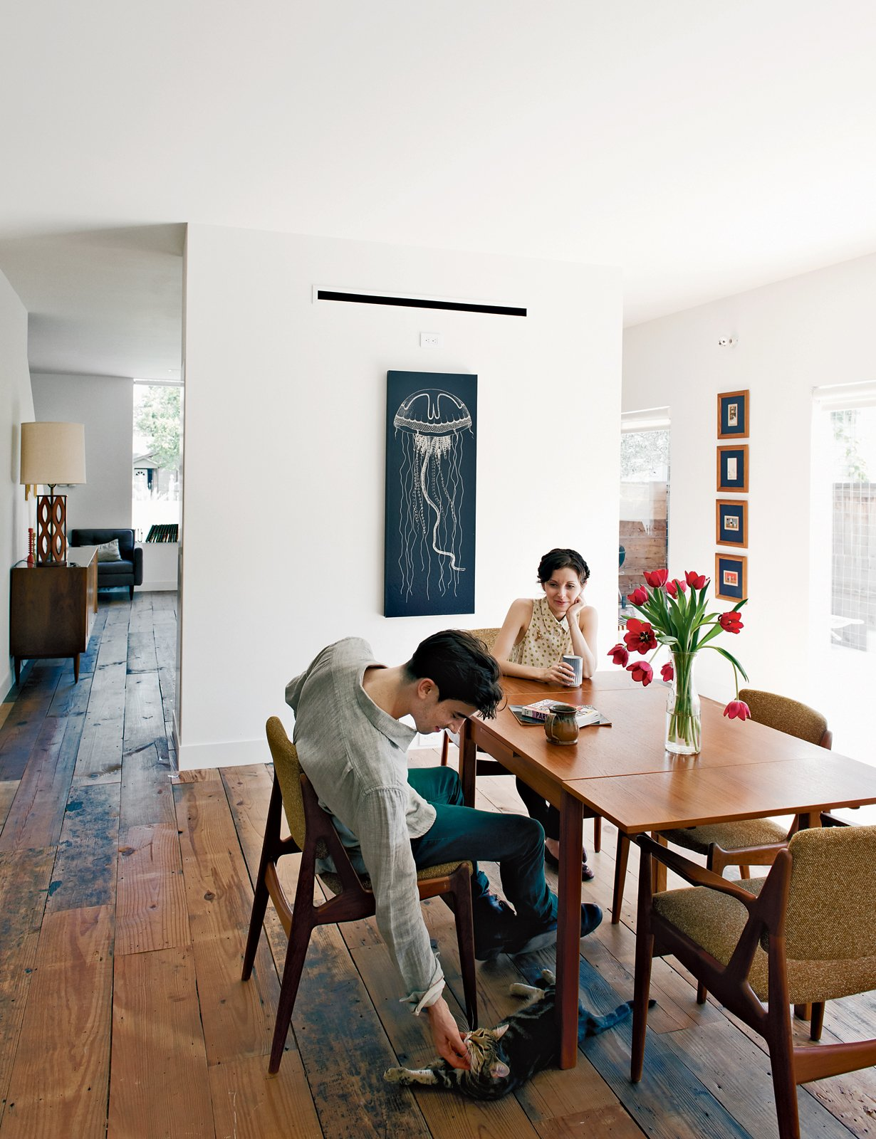 Joseph Walsh and Lauren Strongin, seen here in their dining room, have also kitted out their unit with vintage furniture.