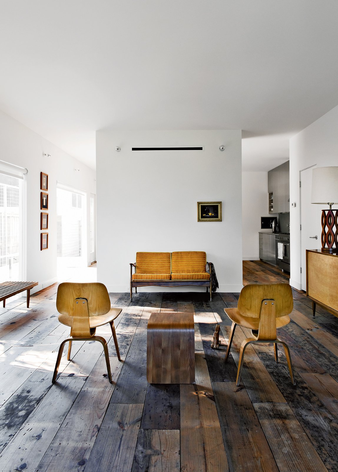 Walsh and Strongin's living room strikes a more rustic note. Tagged: Living Room, Chair, Sofa, and Medium Hardwood Floor.  Photo 14 of 15 in Row on 25th: Affordable Housing Development in Houston