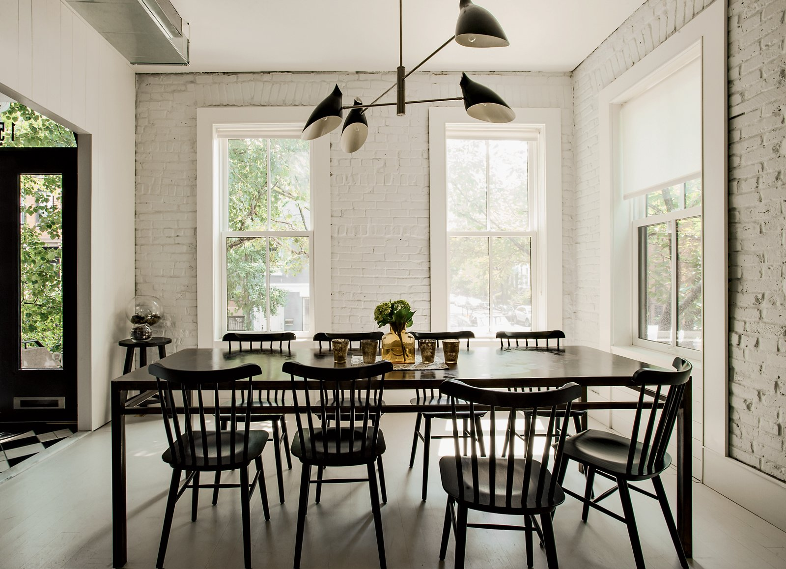 The Torroja pendant light by David Weeks hangs in the dining area, standing in sharp relief to the home's original brick, now painted white (in Benjamin Moore Paper White)along with the wooden floorboards (in Benjamin Moore Revere Pewter). Radiant heat underfoot means a toasty interior even without a surfeit of textiles.