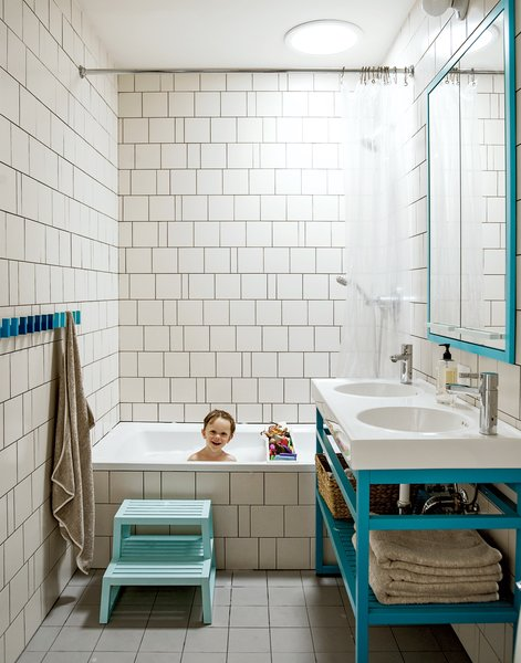 "Bathroom  A creative way of cutting costs is on display in son Nate's bathroom, where the wall tiles are arranged in a whimsical, irregular pattern making use of slim sections of tile cut for transitions and corners. ""We came up with a pattern that could incorporate random sizes so we were able to order the exact amount of tile that we needed,"" Bischoff says. ""It allowed us to get the most out of the tile price because there wasn't that 20 percent that [would normally go] into the landfill."" The two-bowl sink is the Vitviken model from Ikea; it's topped with a chrome Hansgrohe faucet and accented by Ikea's Godmorgon medicine cabinets customized by MADE."
