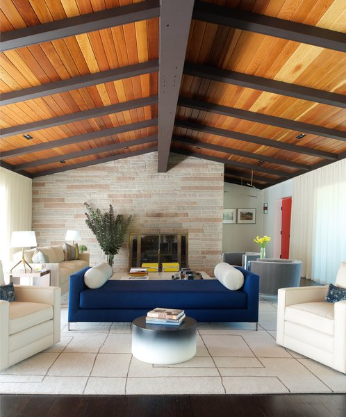 The renovated home maintains its original layout. To refresh the dated appearance of the space, Stonefox added cedar tongue-and-groove panels to the ceiling and refinished the floors. The living room rug is from Creative Matters, the WL Daybed is from Niedermaier, and the circular coffee table is a Tie and Die model from Holly Hunt.