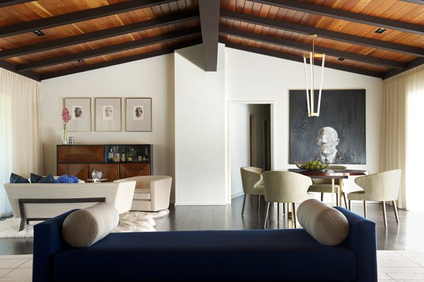 A vintage bar unit, a Tube Chandelier by Michael Anastassiades, and a David Harouni artwork are highlights in the open-plan living and dining space. The architects removed heavy paneling from the walls to lighten the space.