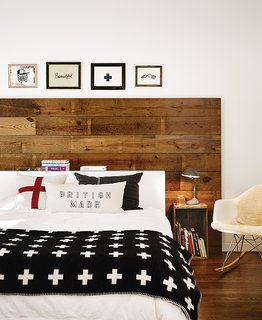 10 Cozy Spaces and 15 Products to Help You Get Ready For Fall - Photo 8 of 10 - Wide shiplap boards were reclaimed from the renovation of a 1920s bungalow in Austin, Texas. At the head of the bed, the wood acts as a focal point and brings a warmth to the space that's complemented by a rustic bedside table, a sheepskin throw on a chair, and an inviting bed layered with blankets and pillows.