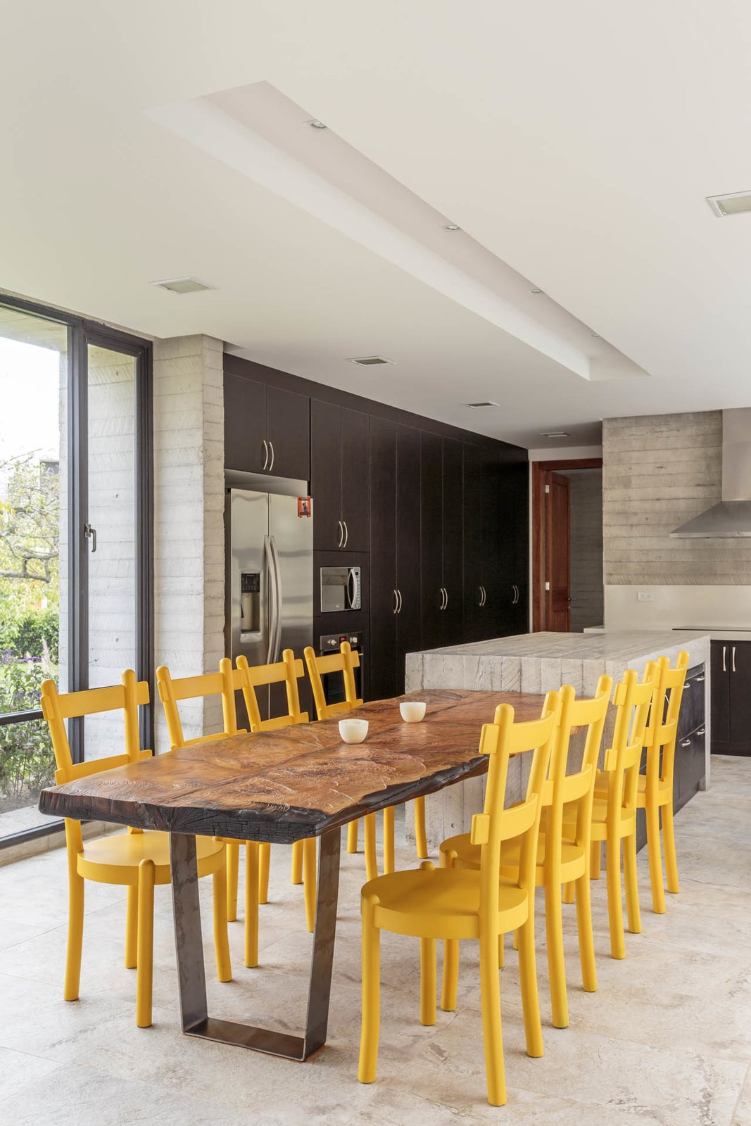 The custom kitchen counters are concrete, and the yellow dining chairs add a welcome splash of color. Tagged: Kitchen and Concrete Counter.  Photo 23 of 25 in 25 Bold Ways to Decorate with Yellow from Uncle Knows Best