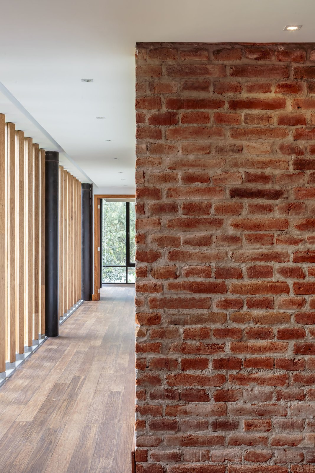 Burneo added exposed brick to his palette of interior materials. Tagged: Hallway and Medium Hardwood Floor.  Photo 6 of 10 in Revealing the Pros and Cons of Exposed Brick and How to Take Care of It from Uncle Knows Best