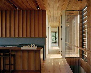 Modern Wood-Lined Family Home in the Hamptons - Photo 4 of 9 - The adjacent open kitchen is made of mahogany (to match the floors, ceilings, and walls), accented by a volcanic stone backsplash and a Viking gas cooktop.