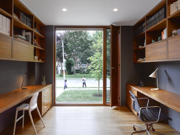 The study features floor-to-ceiling sliding glass doors that bring the outdoors in. Space-saving custom walnut desks are accented by a Pixo Optical LED Table Lamp, an AJ table lamp, and a 1958 Eames Management Chair.