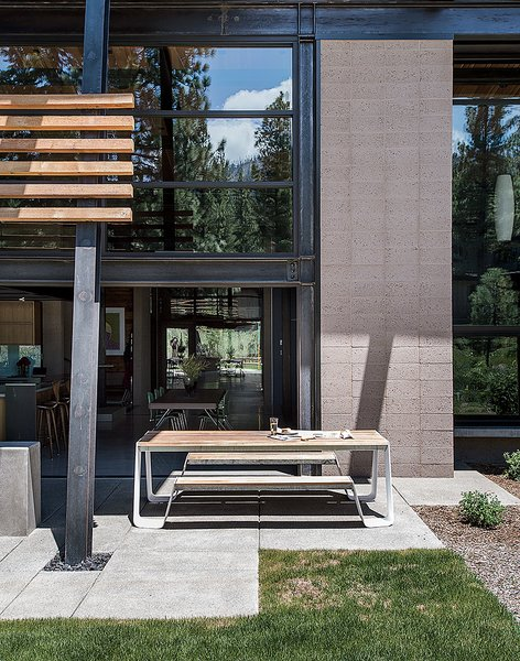 """A picnic table from Janus et Cie sits off the kitchen; the landscape architecture is by Richard D. Wood. In addition to passive solar, says Hawkins, """"there is the added benefit of a thick concrete slab as a thermal mass that absorbs and stores the heat from the sun."""""""